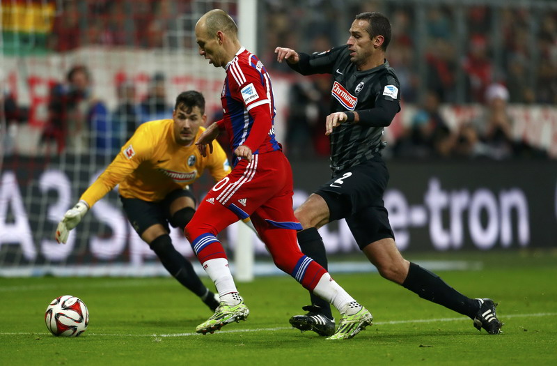 Bayern Munich's Robben fights for the ball with Freiburg's Krmas during their German first division Bundesliga soccer match in Munich